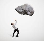 Scared businessman under big flying stone Stock Photo
