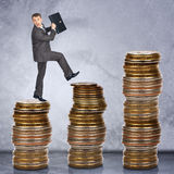 Scared businessman walking on stack of coins Royalty Free Stock Photography