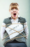 Scared businesswoman bound by contract terms. Royalty Free Stock Image