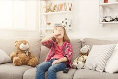 Scared casual little girl watching tv while sitting on sofa at home. Scared little casual girl watching tv. Frightened female kid sitting on sofa, home alone Stock Image