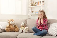 Scared casual little girl watching tv while sitting on sofa at home. Scared little casual girl watching tv. Frightened female kid sitting on sofa, home alone Stock Images