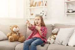 Scared casual little girl watching tv while sitting on sofa at home. Scared little casual girl watching tv. Frightened female kid sitting on sofa, home alone Stock Photos
