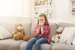 Scared casual little girl watching tv while sitting on sofa at home. Scared little casual girl watching tv. Frightened female kid sitting on sofa, home alone Royalty Free Stock Photography