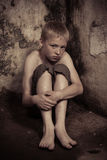 Scared child in corner of dungeon Stock Images