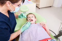 Scared child on drilling procedure in dentist chair. Female or women dentist doctor working with kid patient royalty free stock photo