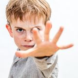 Scared child with hand forwards defending himself or acting bully Royalty Free Stock Photo