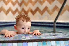 Scared child in pool. Child at the edge of the pool looking scared Royalty Free Stock Photography