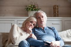 Old age spouses sitting on couch watching thriller movie stock photo