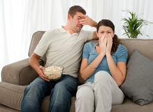 Scared couple watching a horror movie. Scared couple eating pop corn while watching a horror movie at home Stock Image