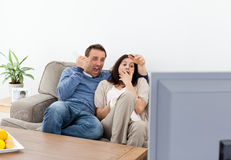 Scared couple watching a horror movie on the tv Stock Images