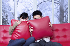 Scared couple watching movie at home Royalty Free Stock Photos