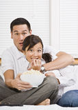 Scared Couple Watching TV. A young, attractive couple is sitting together in bed and watching TV.  They look shocked or scared, and are looking at the camera Royalty Free Stock Photography