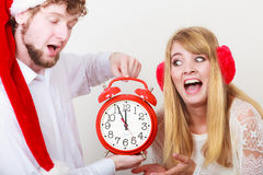 Scared couple woman and man with alarm clock. Stock Photo