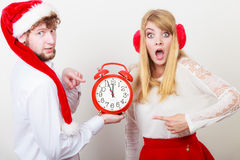 Scared couple woman and man with alarm clock. Royalty Free Stock Image