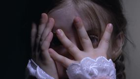 Scared cute little girl covering face with hands, danger or domestic violence. Stock footage stock footage