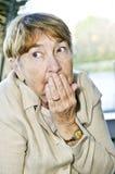 Scared elderly woman. Afraid elderly woman looking sideways in fear stock image