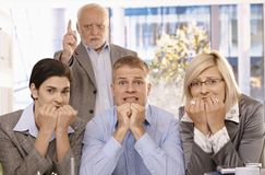 Scared employees sitting with angry boss behind. Scared employees sitting with hands up to mouth, angry boss standing behind pointing Royalty Free Stock Photo
