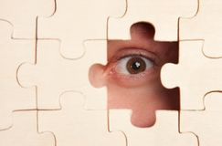 Scared eye watching through puzzles Stock Photo