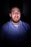 Scared face in the dark. A bearded man screaming in the dark and has a frightened look on his face Royalty Free Stock Photos