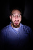 Scared face in the dark. A bearded man screams and has a frightened look on his face Stock Images