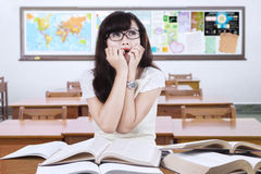 Scared female learner sitting in the classroom Royalty Free Stock Photos
