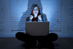 Scared female teenager with computer laptop suffering cyberbullying and harassment being online abused. Sad and scared female teenager with computer laptop Royalty Free Stock Images