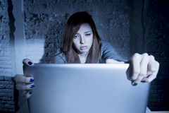 Scared female teenager with computer laptop suffering cyberbullying and harassment being online abused Stock Photo