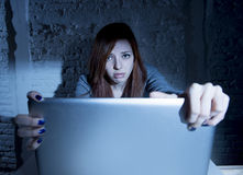 Scared female teenager with computer laptop suffering cyberbullying and harassment being online abused Stock Photos