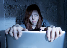 Scared female teenager with computer laptop suffering cyberbullying and harassment being online abused. Sad and scared female teenager with computer laptop Stock Image