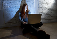 Scared female teenager with computer laptop suffering cyberbullying and harassment being online abused. Sad and scared female teenager with computer laptop Royalty Free Stock Photos
