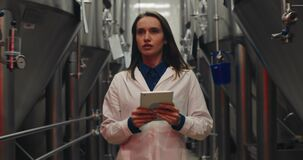 Scared female worker in white lab coat holding tablet and walking through rows of steel brewing vats. Alert signals and