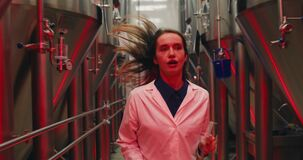 Scared female worker in white lab coat running with tablet through rows of steel brewing vats. Alert signals and red