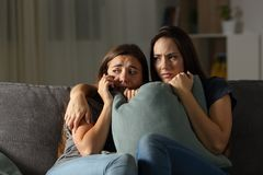 Scared friends at home calling police. Sitting on a couch in the living room at home Royalty Free Stock Photos