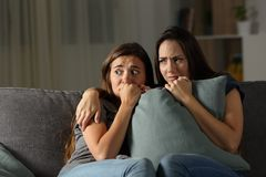 Scared friends listening noise at home in the night. Sitting on a couch in the living room at home Stock Photography