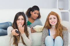 Scared friends with remote control and popcorn bowl at home Stock Photos
