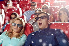 Scared friends watching horror movie in 3d theater Royalty Free Stock Images