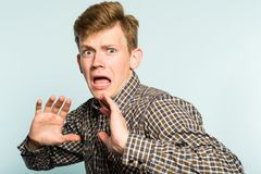 Scared frightened man cowardly comical reaction. Scared frightened man. cowardly comical reaction. portrait of a young guy on light background. emotion facial Royalty Free Stock Photos