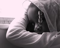 Scared Girl. A scared abused young black girl looks worried as she stares at the camera stock image