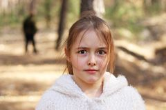 Scared girl alone in the forest, man on background stock image