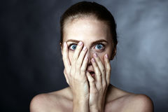 Scared girl covering her face with her hands Royalty Free Stock Photography