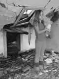 Scared girl in destroyed house. One sad and depressed young child with bear toys standing  in destroyed house. Vertical photo black and white Royalty Free Stock Photography
