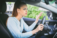 Scared girl driving a car. Scared pretty girl driving a car. Shocked woman in an automobile stock image