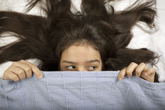 Scared girl hiding in bed. Young girl is hiding in the bed Royalty Free Stock Photos