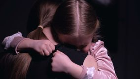 Scared girl hiding in mothers embrace, victims of domestic violence, close-up. Stock footage stock footage