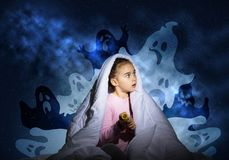 Scared girl with pillow hiding under blanket stock image
