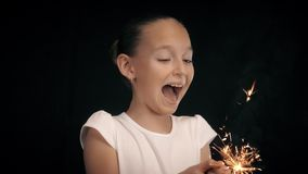 Scared girl holding in hands burning sparkler with hot sparks on black background. Screaming teenager girl with hot bengal light. Dangerous holiday fireworks stock footage