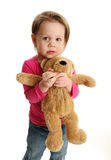 Scared girl holding a teddy bear Stock Photography