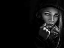 Scared girl in hood. Looking at camera on black background with copyspace monochrome Stock Photography