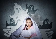 Scared girl with pillow hiding under blanket stock photo
