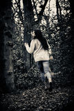 Scared girl running. Teenage girl running scared away from camera in woods royalty free stock photography